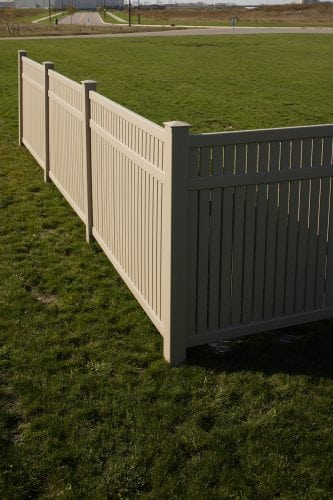 Light woodgrain vinyl fence residential yard