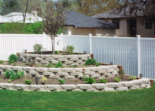 landscaped yard corner stone feature White Vinyl Fence